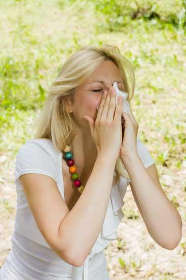 Young woman blowing nose outdoor, pollen allergy,